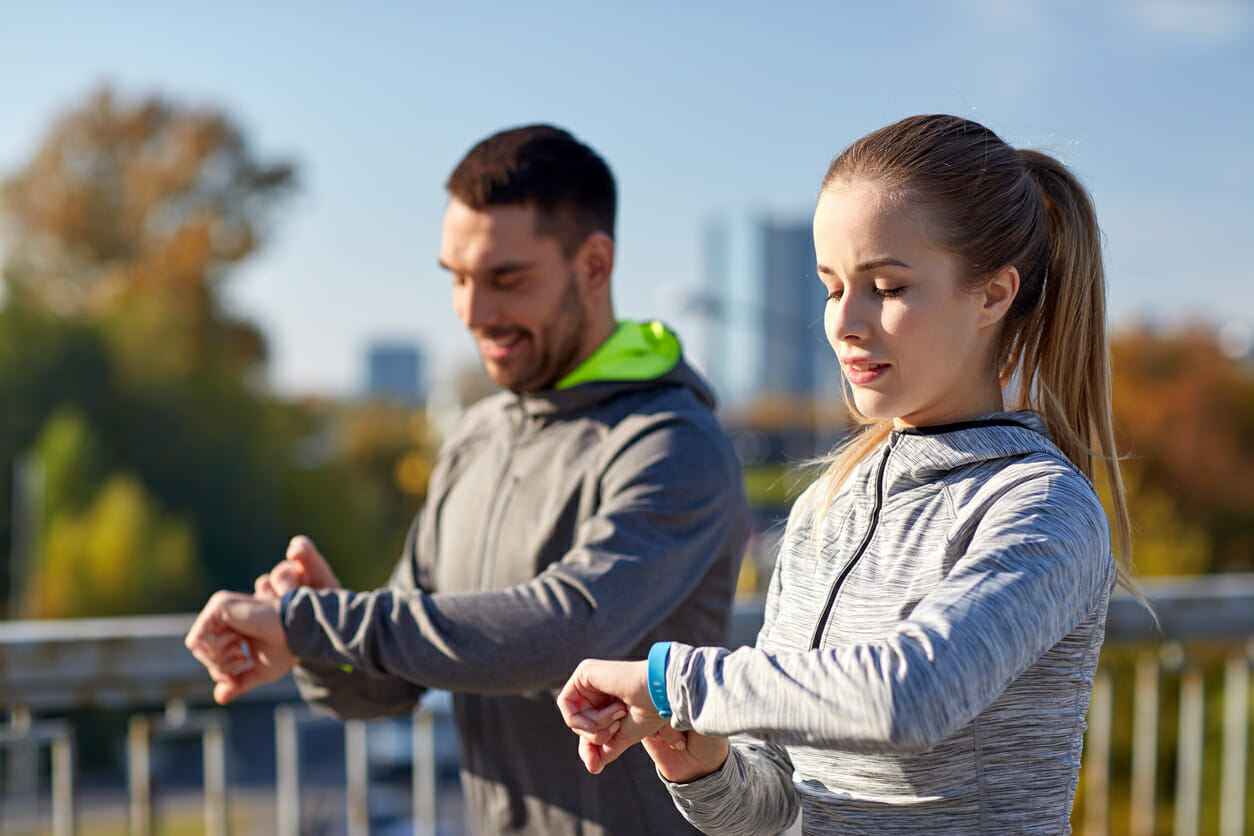 couple with fitness trackers training in city rpt utah