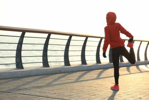 Young fitness woman runner warm up at sunrise seaside