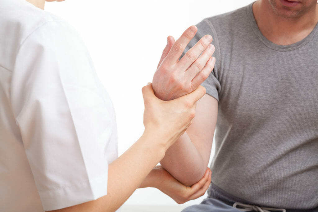 physical therapist assisting with arm and joint pain