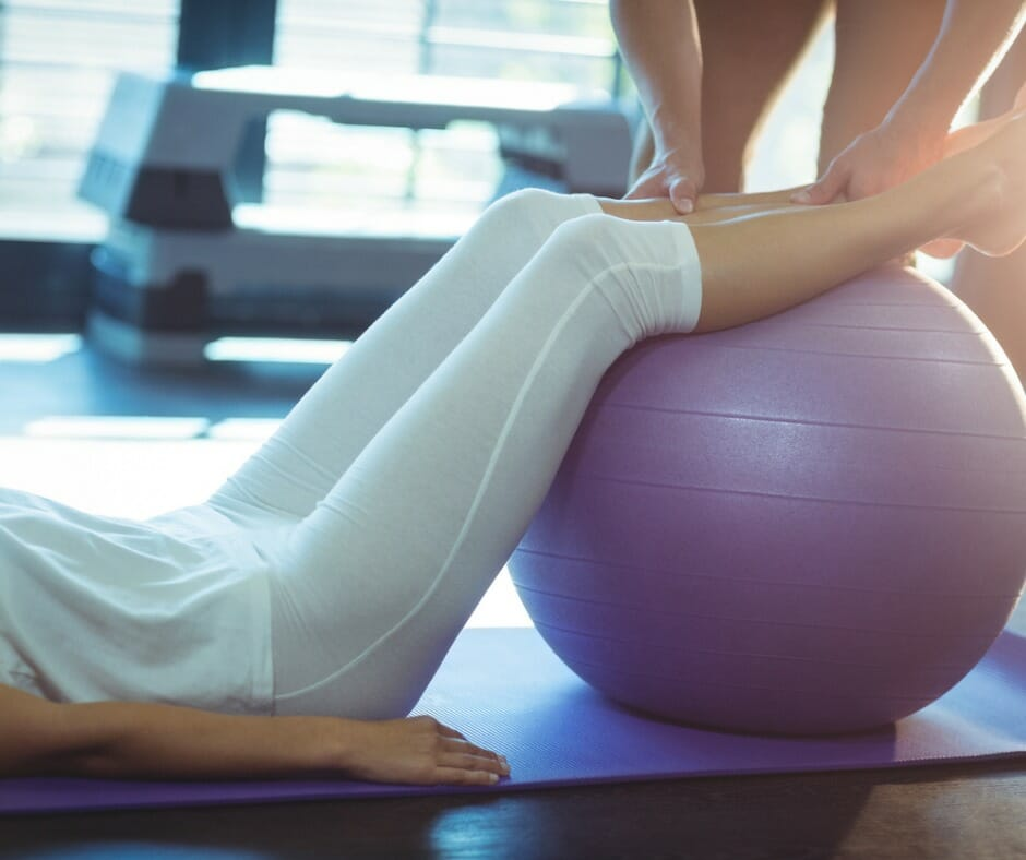 Physiotherapist assisting a patient with exercise ball picture id614014696