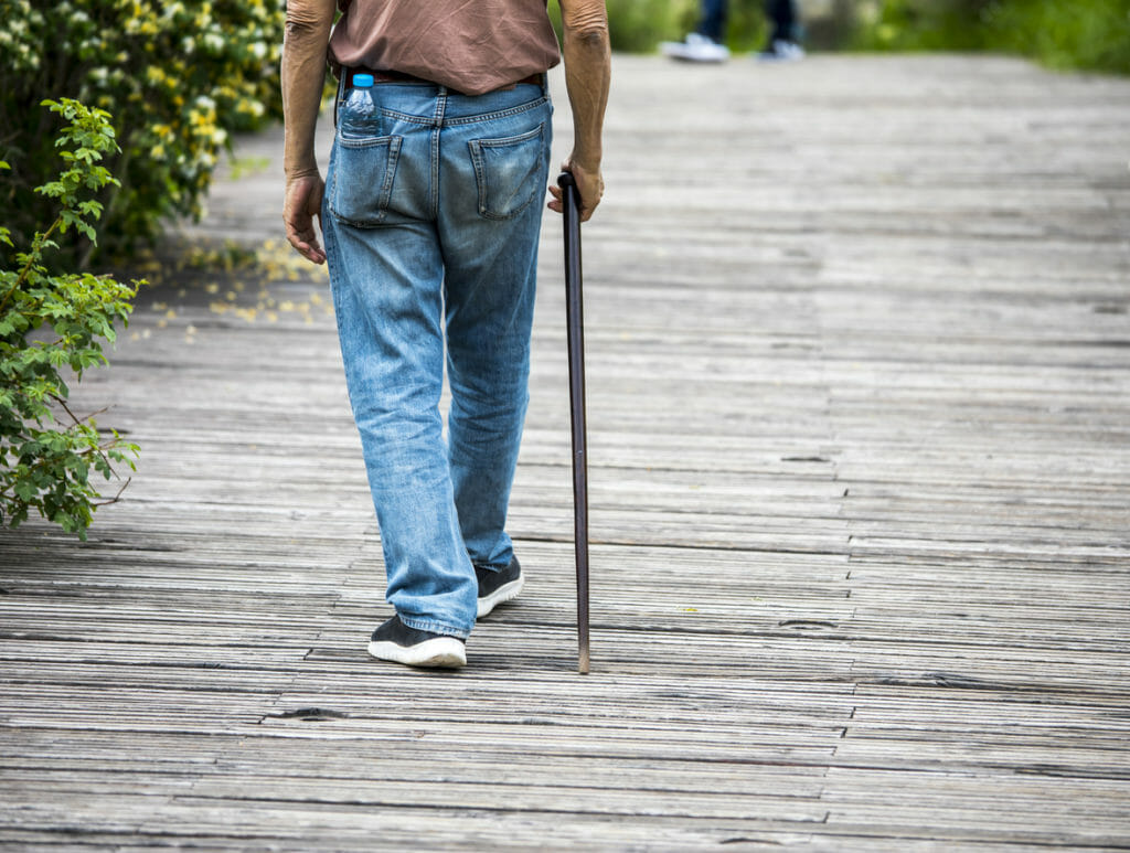 Elderly man with cane on the wood street