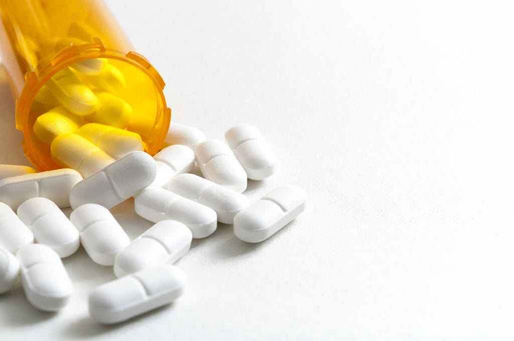 Hydrocodone capsules spilling out of a prescription bottle with copyspace