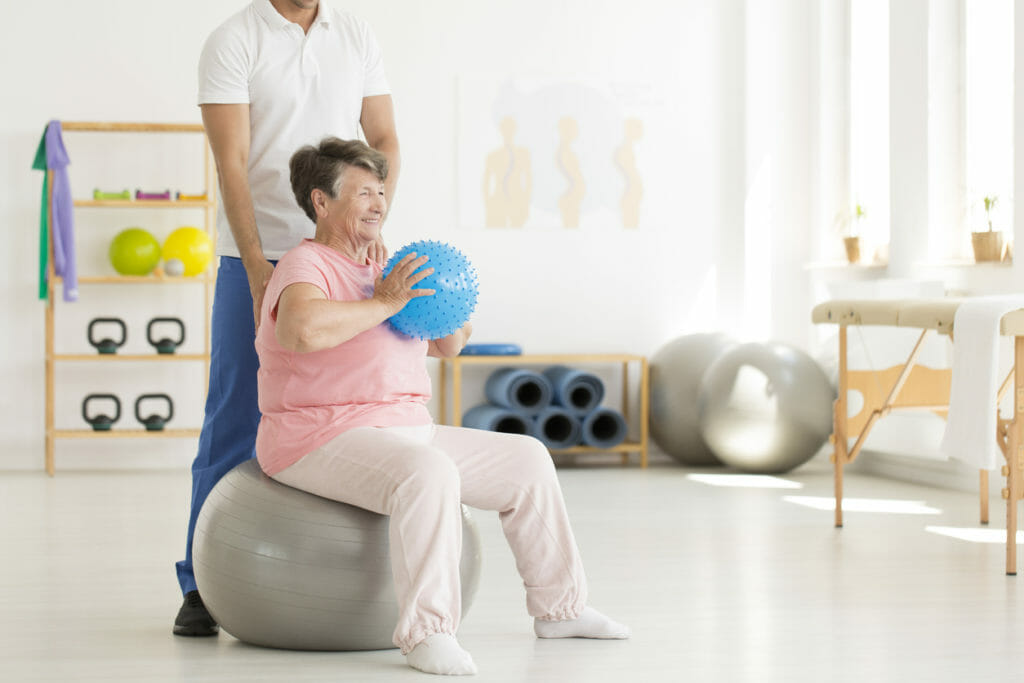 Senior woman exercising in clinic
