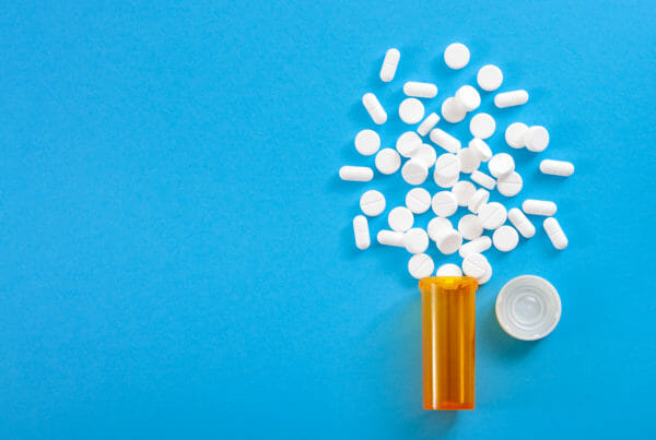 Pills falling from pill bottle on blue background with copyspace