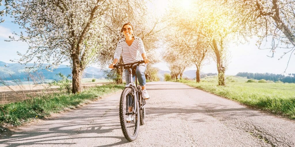 Happy smiling woman rides a bicycle on the country road under blossom trees. Spring is comming concept image.