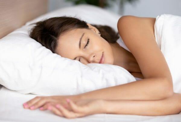 Serene calm young woman sleeping well on orthopedic soft pillow