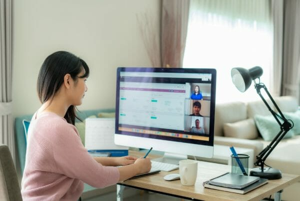 Back view of Asian business woman talking to her colleagues about plan in video conference. Multiethnic business team using computer for a online meeting in video call. Group of people smart working from home.