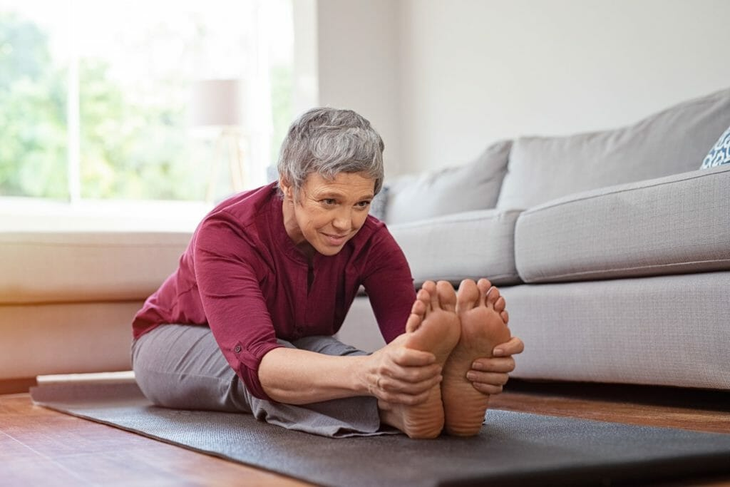 Mature woman doing yoga exercise at home